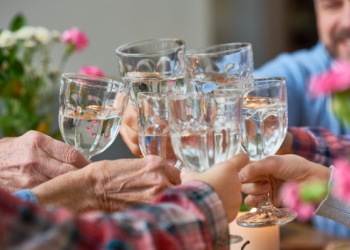Close-up of united family clinking glasses of water together
