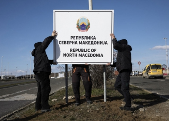 """Workers erect a new road sign reading """"Republic of North Macedonia"""" at the Greece-Macedonia Bogorodica border crossing near Gevgelija, Republic of North Macedonia, on Wednesday, February 13, 2019. A former Yugoslav republic thats been blocked from joining NATO and the European Union because of a dispute over its name has started using a new moniker thats the result of a deal to open the doors to western integration. Photographer: Konstantinos Tsakalidis/Bloomberg via Getty Images"""