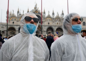 Tourists wear protective face masks at Venice Carnival, which the last two days of, as well as Sunday night's festivities, have been cancelled because of an outbreak of coronavirus, in Venice, Italy February 23, 2020. REUTERS/Manuel Silvestri