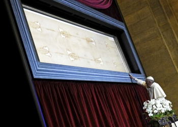 FILE PHOTO: Pope Francis touches the Shroud of Turin during a two-day pastoral visit in Turin, Italy, June 21, 2015. REUTERS/Giorgio Perottino/File Photo