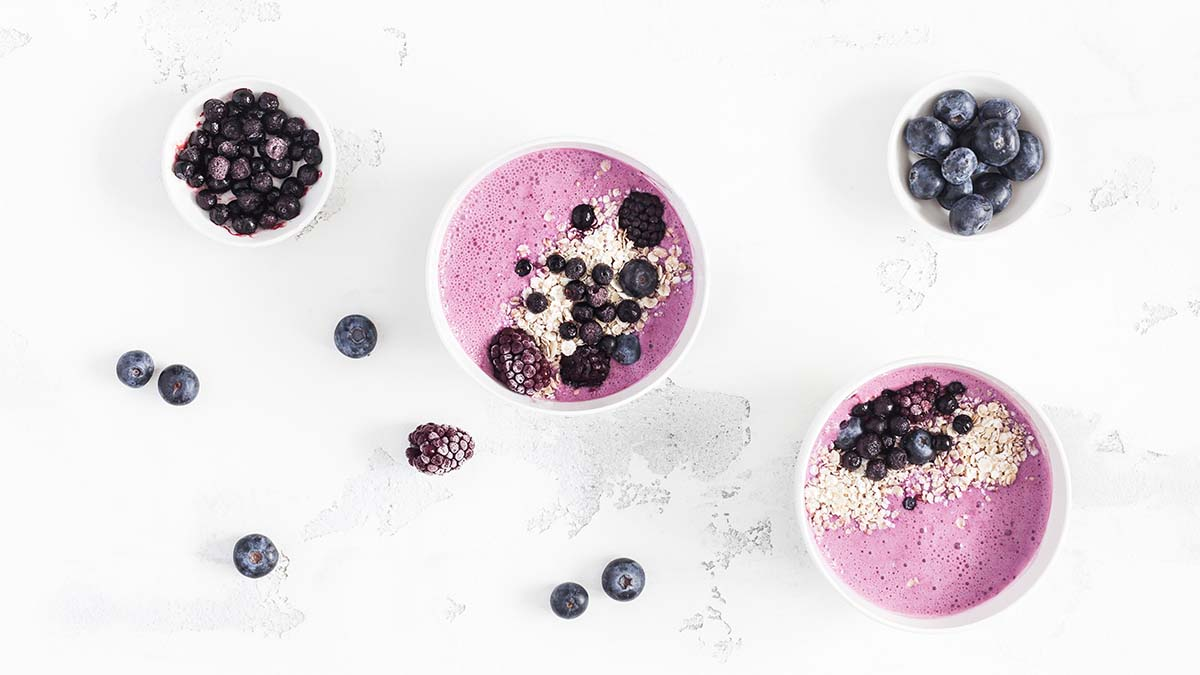 Breakfast with muesli, acai blueberry smoothie, fruits on white background. Healthy food concept. Flat lay, top view