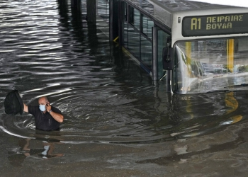 The driver of the bus speaks on his mobile phone as he wades through high water after evacuating the passengers from the bus stuck in a flooded underpass in southern Athens, Thursday, Oct. 14, 2021. Storms have been battering the Greek capital and other parts of southern Greece, causing traffic disruption and some road closures. (AP Photo/Thanassis Stavrakis)